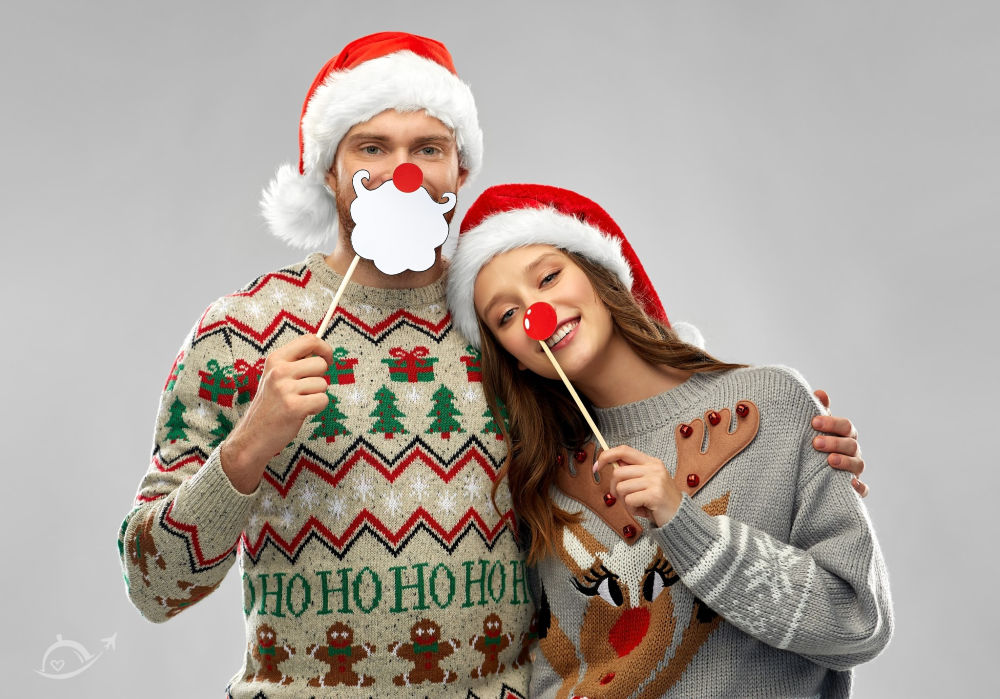 Young couple wearing ugly Christmas sweaters & Santa hats | A Reinvented Mom #funchristmaspartyideas