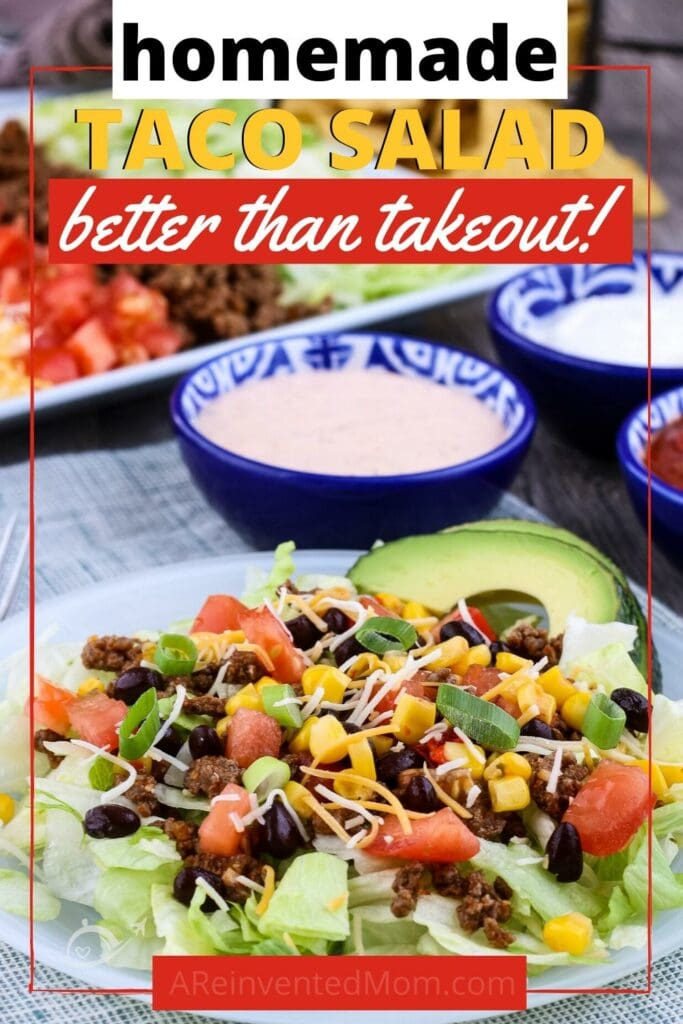 Taco salad with lettuce, ground beef, black beans, corn & cheese on a white plate with Homemade Taco Salad Better than Takeout Graphic | A Reinvented Mom