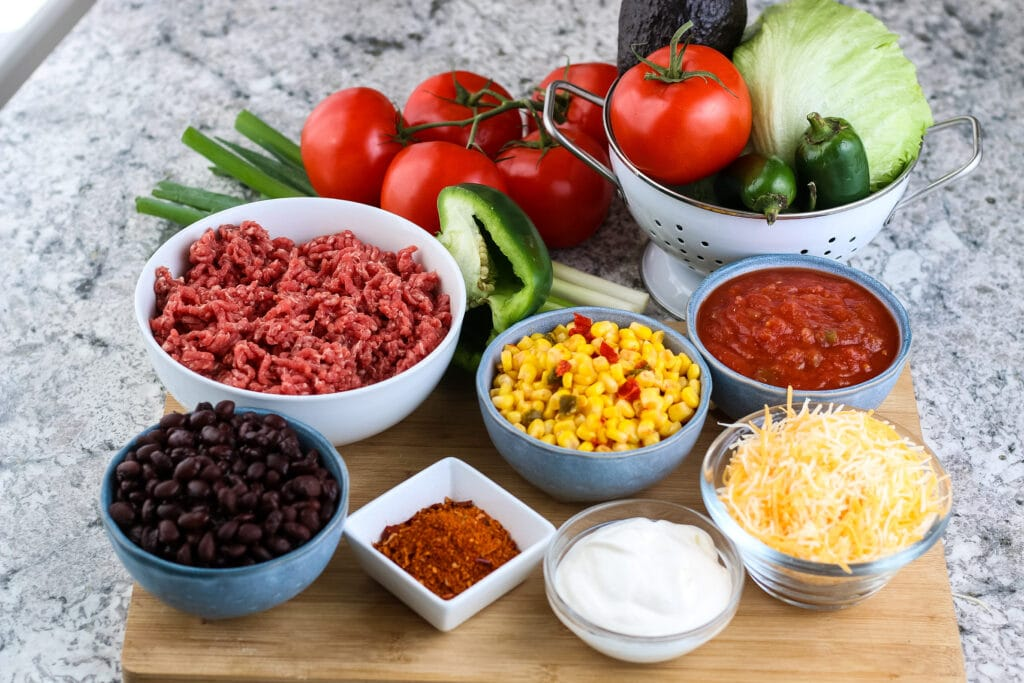 Bowls filled with ingredients for Homemade Taco Salad on wooden surface | A Reinvented Mom