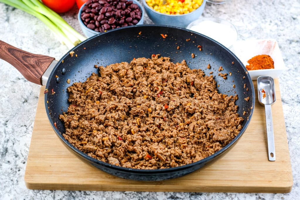 Skillet with seasoned, cooked ground beef taco meat | A Reinvented Mom