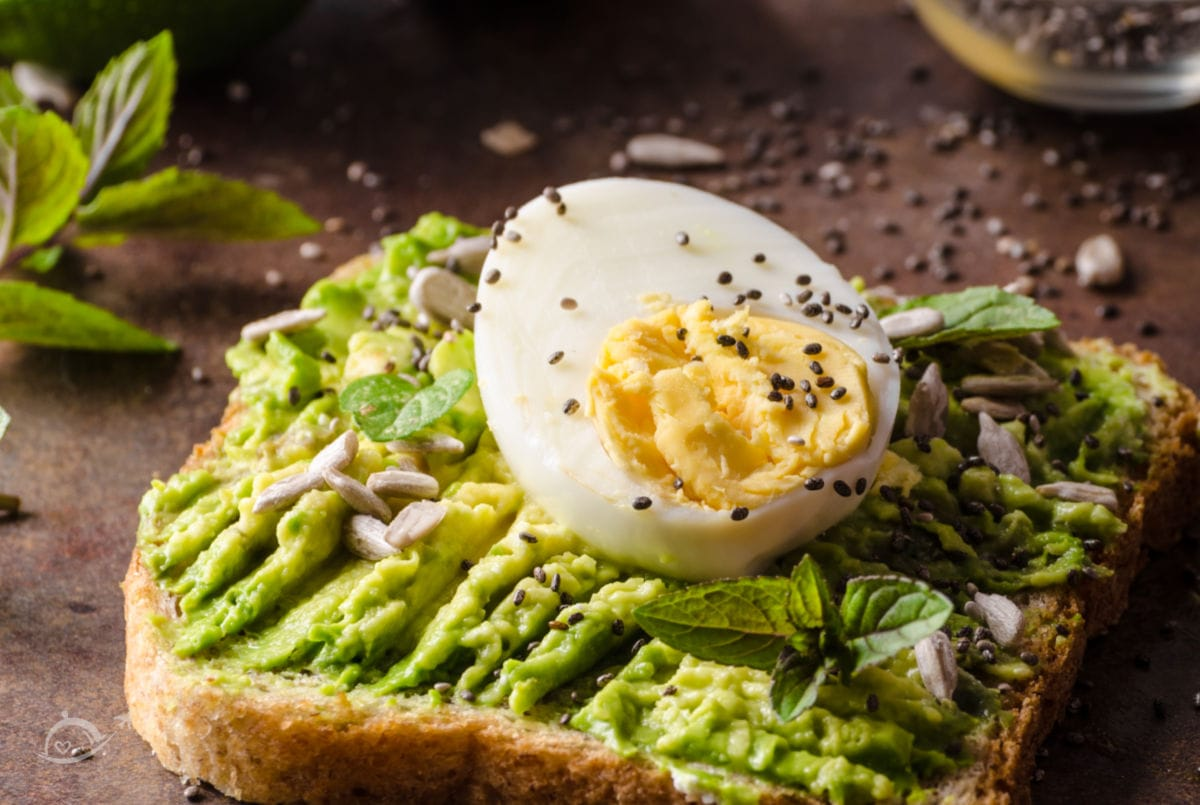A slice of bread with mashed avocado, hard boiled egg slice & sunflower seeds on a stone background. Recipes with Boiled Eggs | A Reinvented Mom