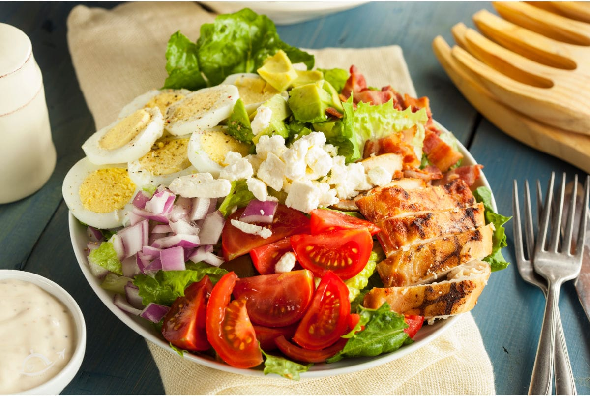 A white bowl filled with Cobb Salad (grilled chicken, tomato, red onion, cheese, boiled egg, avocado, bacon & greens).