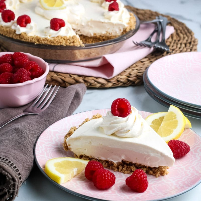 A slice of Lemonade Pie garnished with whipped cream, berries & lemon slices on a pink plate. A bowl of raspberries & partial pie in the background | A Reinvented Mom