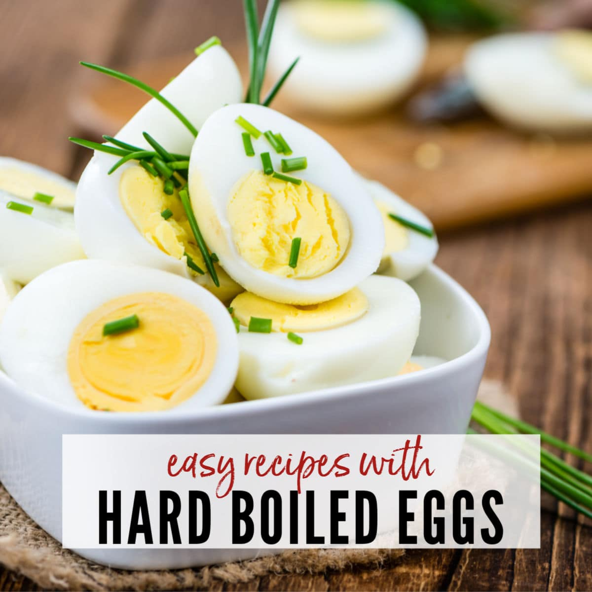 A white bowl filled with sliced boiled eggs with chive garnish on a wooden table with Easy Recipes with Boiled Eggs graphic | A Reinvented Mom