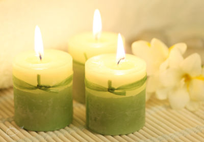 Spa candles with white flowers in the background.