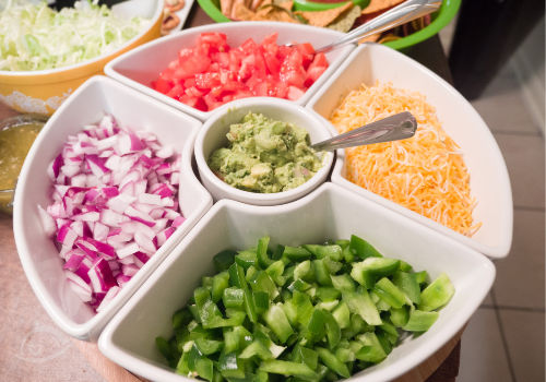 Chopped onions, peppers, tomatoes, shredded cheese & guacamole in a divided bowl. | How to Throw a Taco Party | A Reinvented Mom