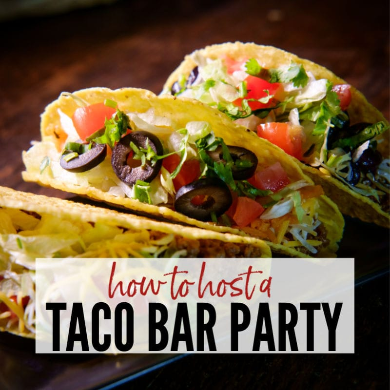 Three loaded  tacos on a dark plate with How to Host a Taco Bar Party graphic | A Reinvented Mom