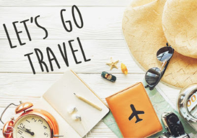 Various travel items on a white wooden flatlay with Let's Go Travel.