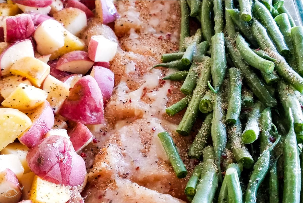 chicken potato green bean bake in a glass dish topped with italian dressing seasoning drizzled with butter