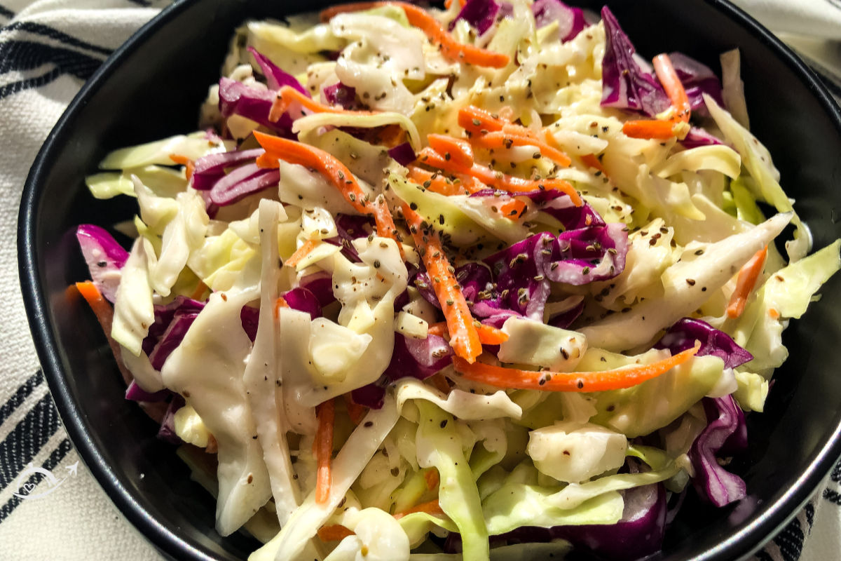 Simple southern coleslaw topped with black pepper after it has been mixed.