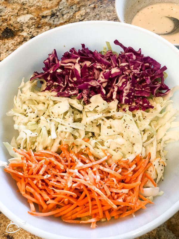 shredded carrots, red cabbage, and regular cabbage in a white bowl ready to make southern coleslaw