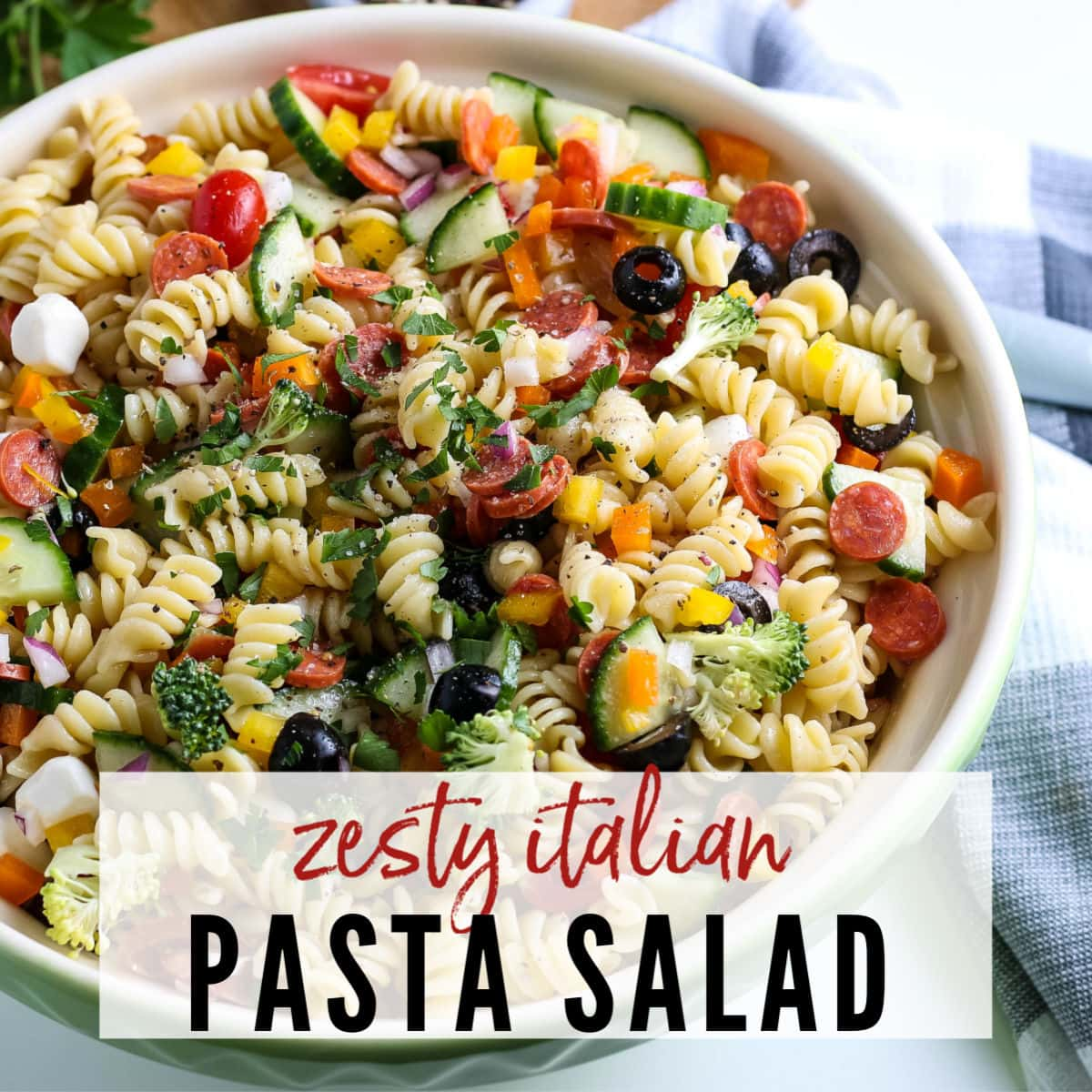 White bowl filled with pasta salad with fresh veggies, cheese & pepperoni