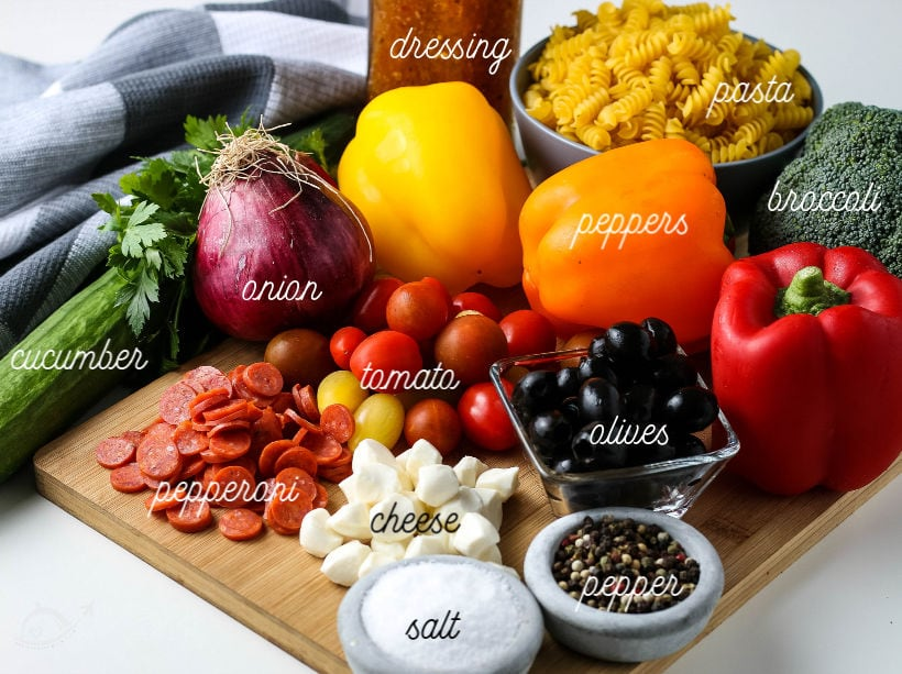 All the ingredients needed for zesty italian pasta salad on a cutting board