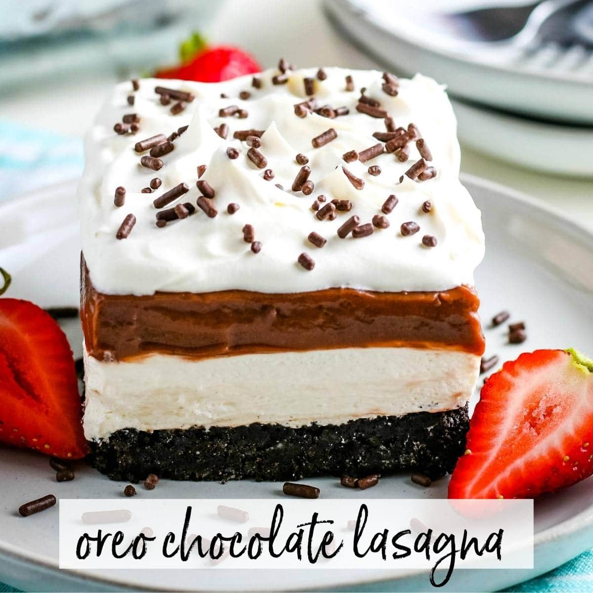 Slice of Oreo Chocolate Lasagna with sliced strawberries on a white plate with graphic overlay.
