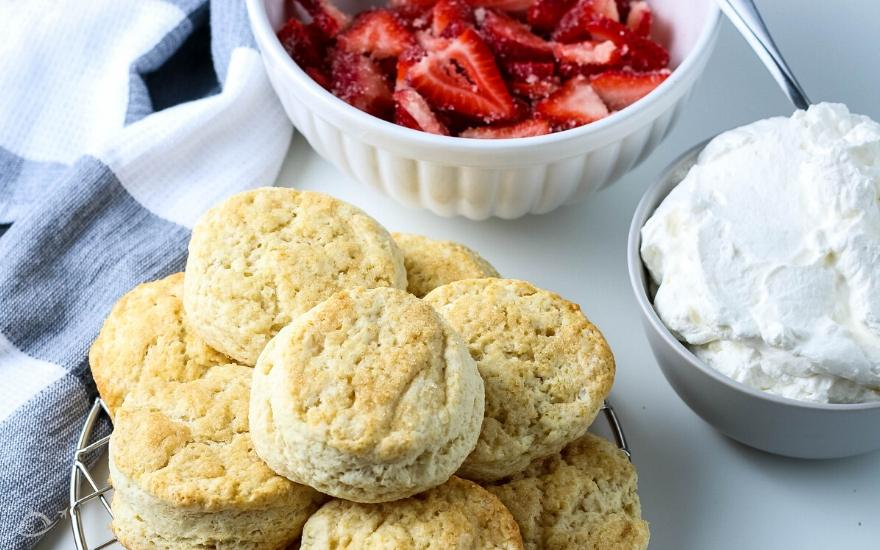 Buttermilk biscuits next to a bowl of strawberries and whipped cream