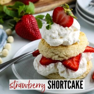 Sliced homemade biscuit with whipped cream & strawberries on a white plate with Strawberry Shortcake graphic | A Reinvented Mom