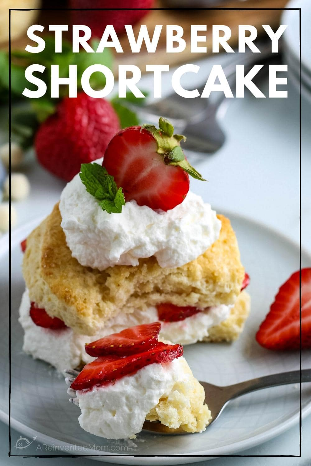 A bite of Strawberry Shortcake on a fork with sliced biscuit, whipped cream and strawberries on a white plate.