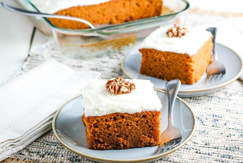 2 cake squares on blue plates with fork, pumpkin cake in casserole dish in the background