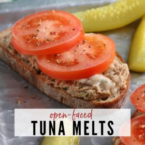 closeup of open faced tuna melt after cooking next to pickle spears