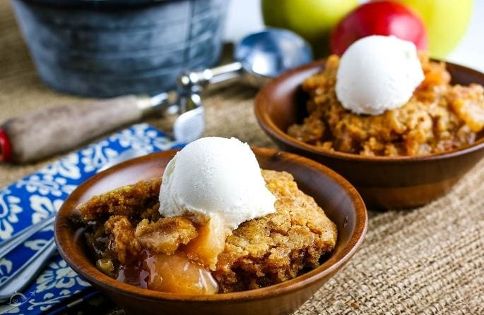 2 wooden bowls filled with apple dump cake and a scoop of vanilla ice cream