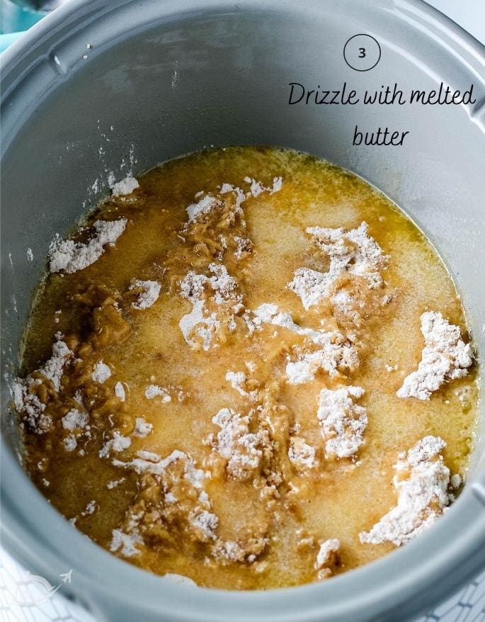 apple dump cake in a crockpot before baking after butter has been drizzled