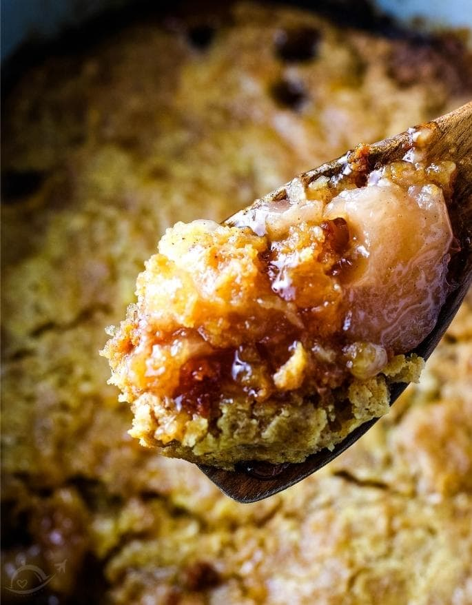 apple dump cake on a spoon with the rest in the background