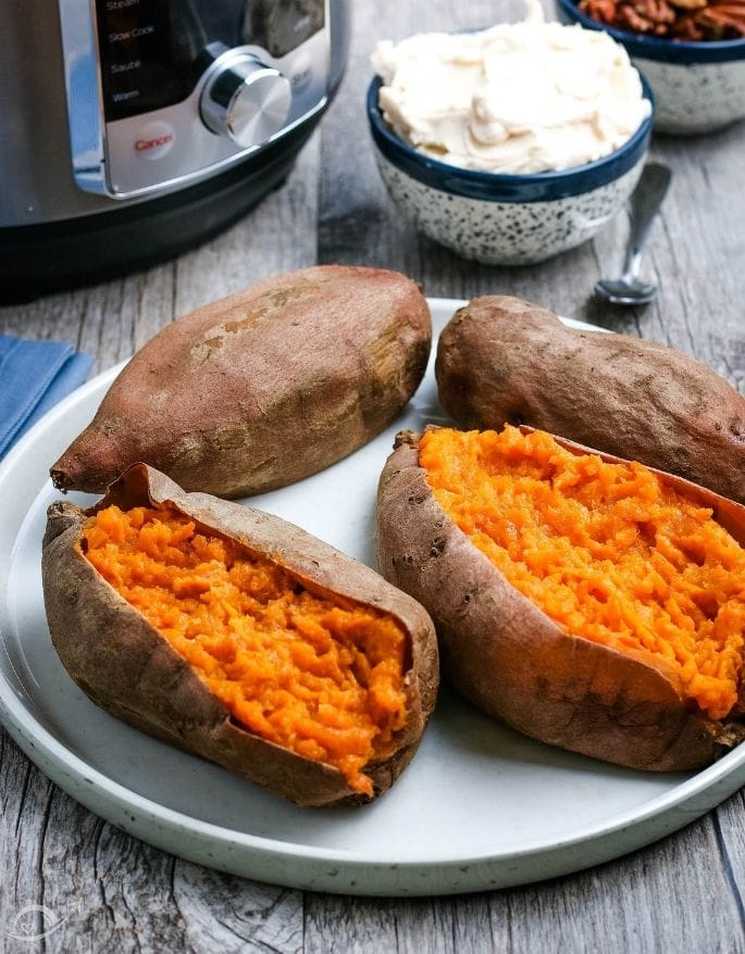 Baked sweet potatoes after cooking next to butter on a white plate