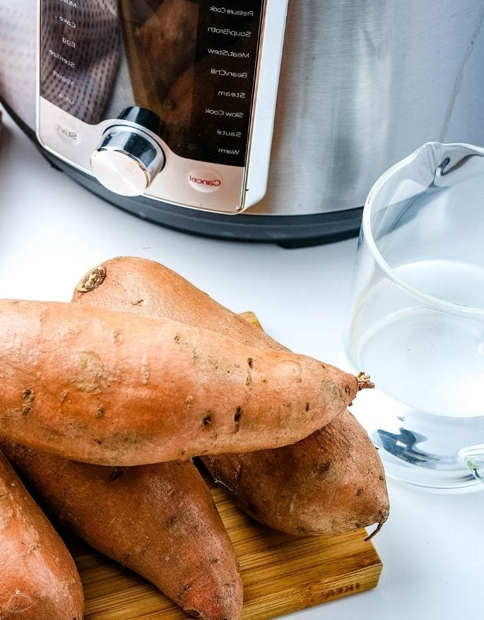 sweet potatoes and water sitting next to an Instant Pot pressure cooker