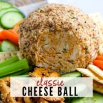 close up of a cheese ball rolled in pecans next to veggies and crackers