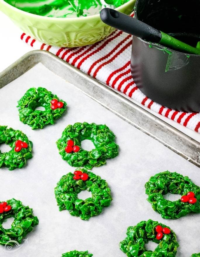 christmas cornflake wreath cookies with red candies on parchment paper