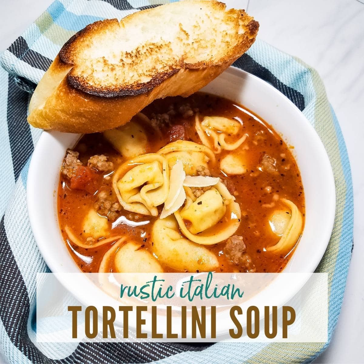 White bowl filled with tortellini soup & a slice of bread with striped towel and graphic overlay.