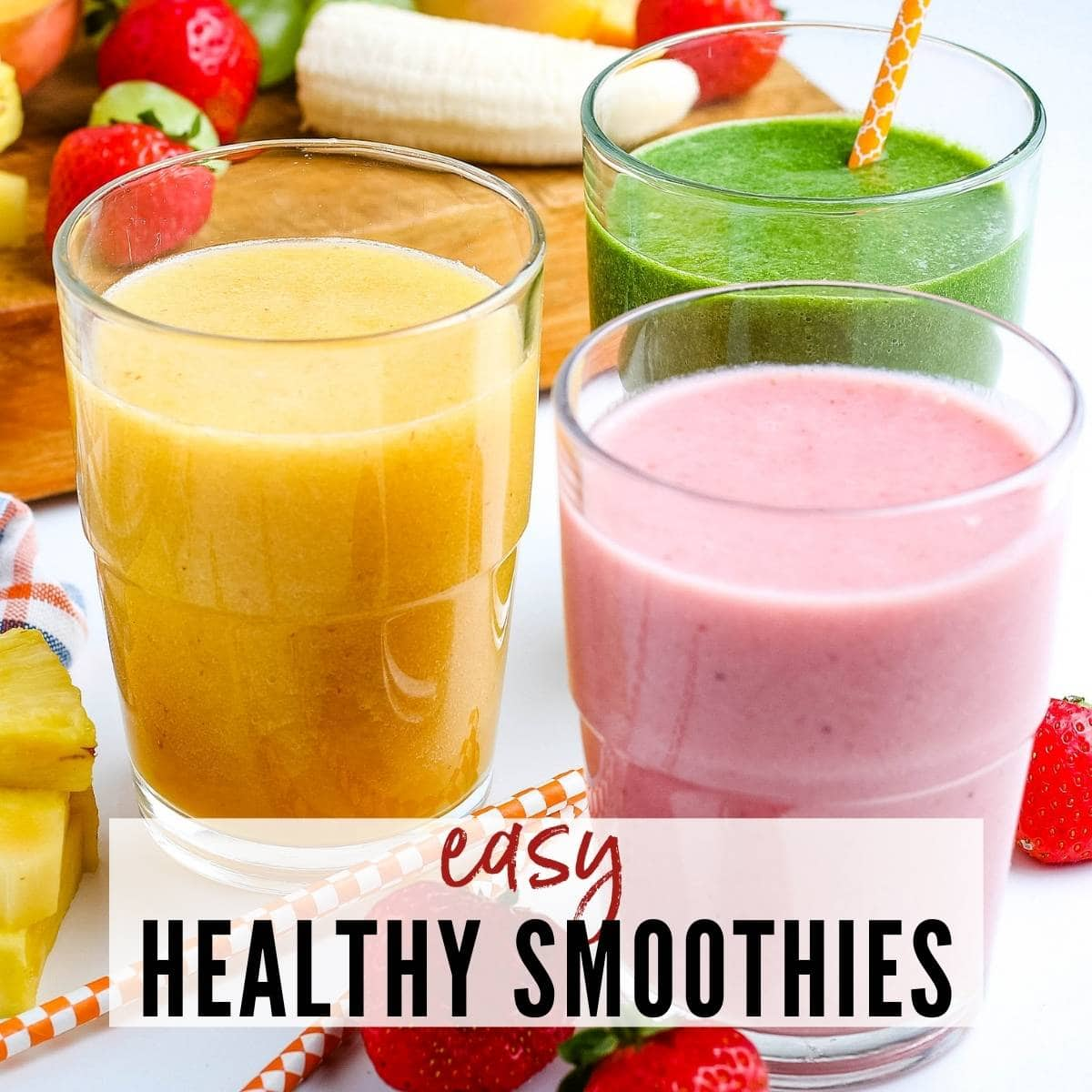 Three glasses of smoothies with fruit in the background