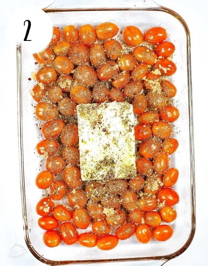 cheery tomatoes and feta block in a glass baking dish