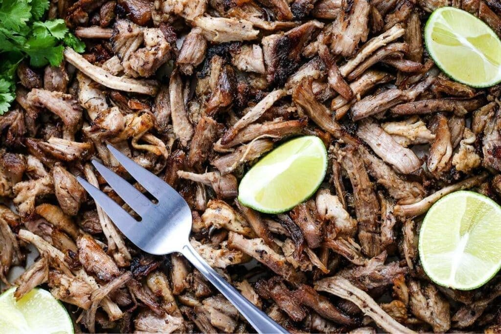 top show of mexican pulled pork with a silver fork and lime wedges