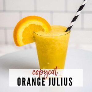 closeup of copycat Orange Julius with black & white straw & orange slice garnish on white background