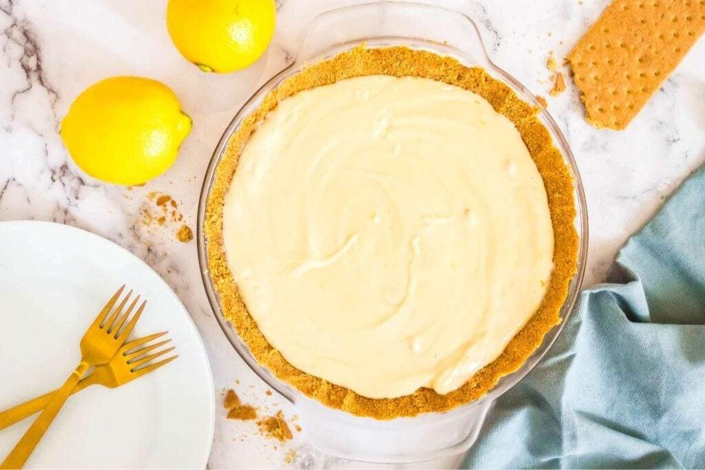 top view of lemon icebox cake in graham cracker crust next to lemons