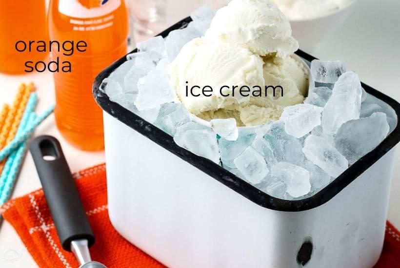 ice cream in a bucket with ice next to orange soda