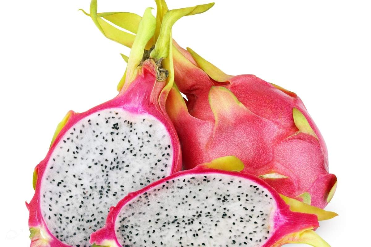 dragon fruit cut in half in front of a whole pitaya