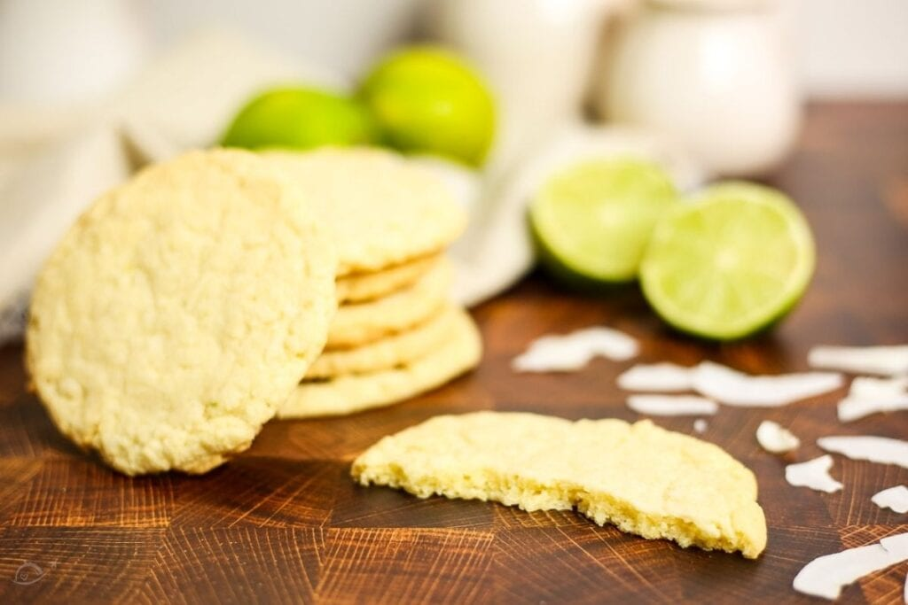 close up of a stack of coconut lime cookies, one is split in half on the counter