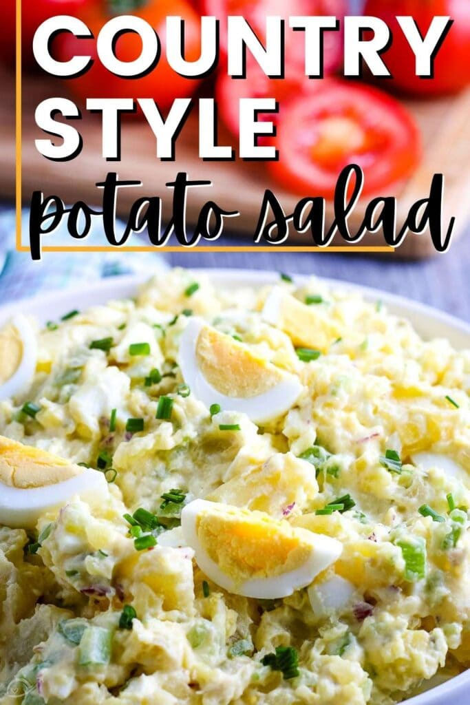 closeup view of a white bowl of country style potato salad with sliced tomatoes in the background and a graphic overlay