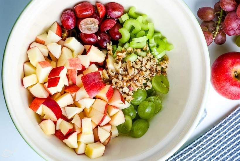 diced apples, halved grapes, chopped celery, and walnuts in a mixing bowl