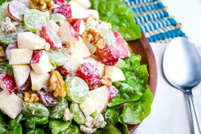 close up of waldorf salad in a brown bowl next to spoon