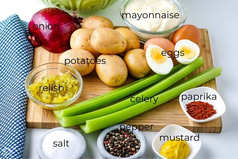 labeled ingredients to make country style potato salad on a wooden cutting board